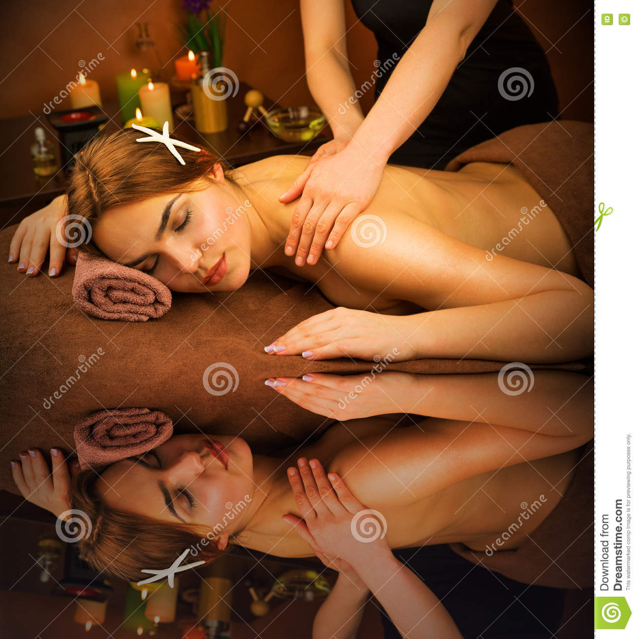 Beautiful woman in spa salon having massage with water reflection