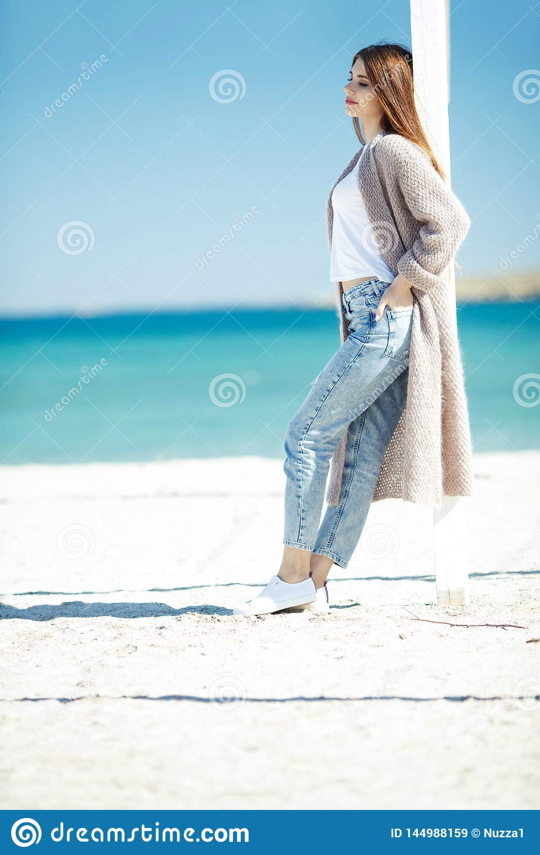 Beautiful woman in spring rests by the sea.