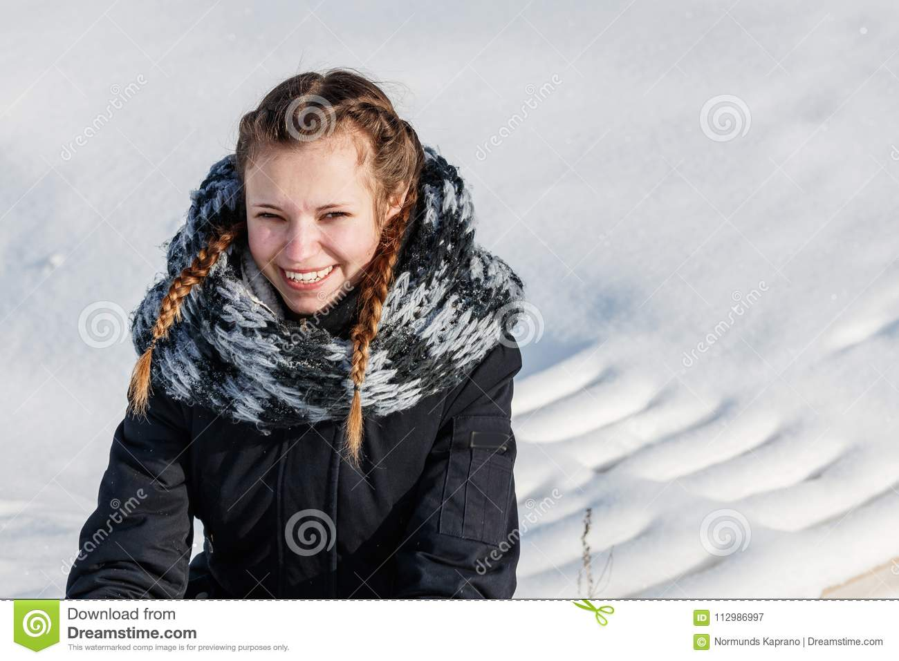 beautiful woman stands in white snow clearing