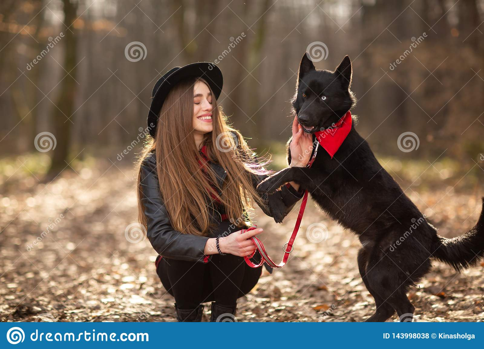 Beautiful woman stroking her dog outdoors. Pretty girl playing and having fun with her pet by name Brovko Vivchar