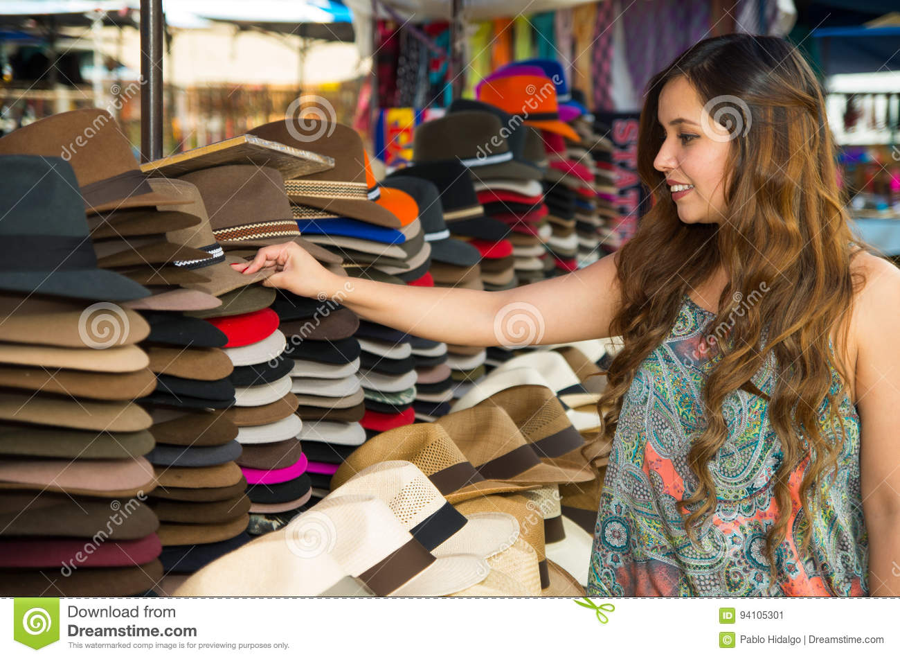 Beautiful woman touching a handmade Panama Hat at the craft market in Otavalo, Ecuador, colorful fabrics background