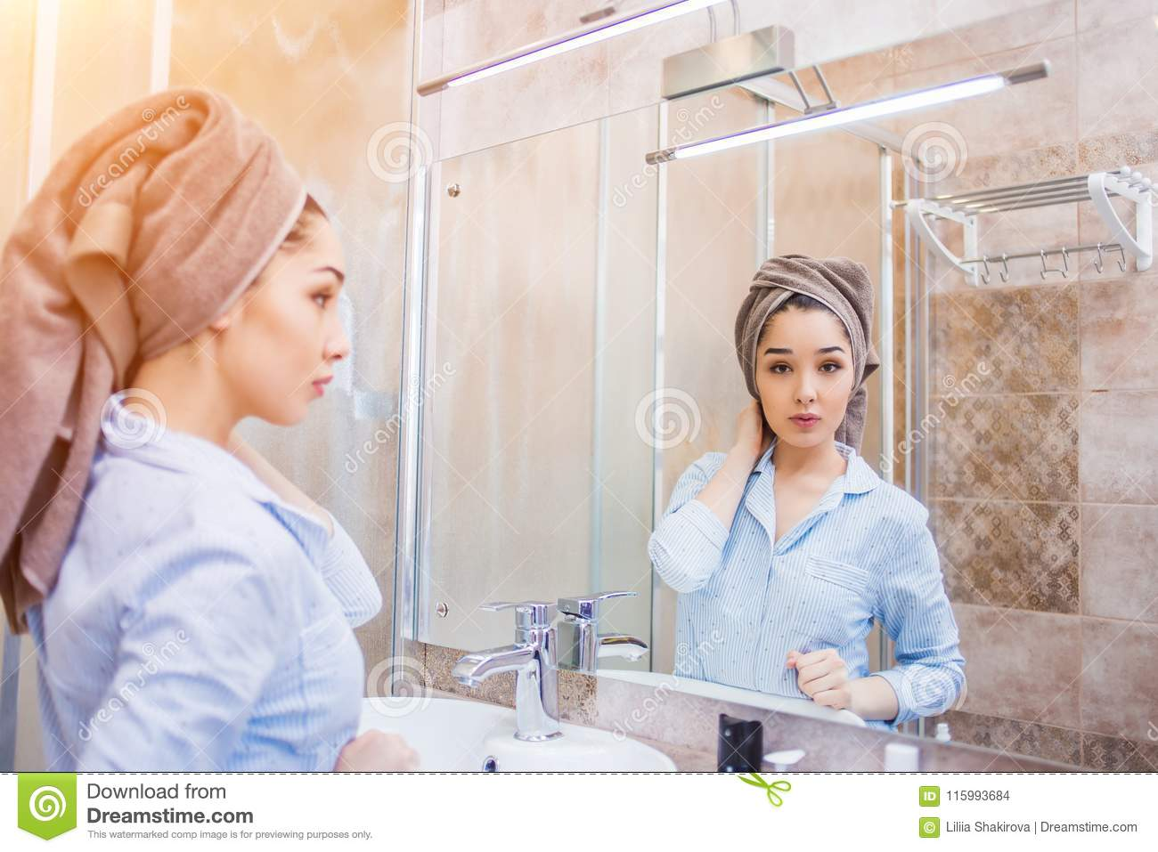 Beautiful woman in towels standing in bathroom after shower.