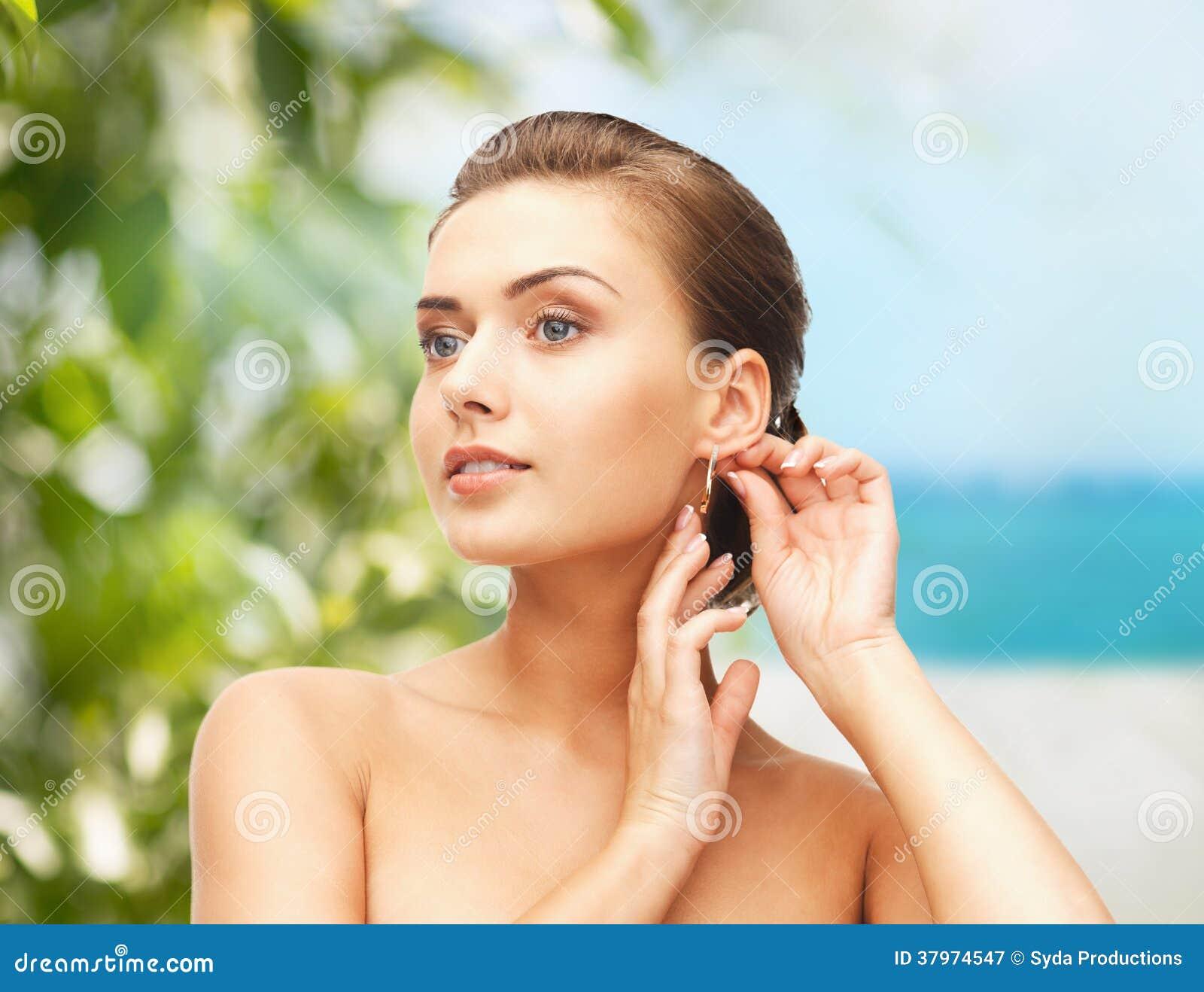 Beautiful woman trying on gold earrings