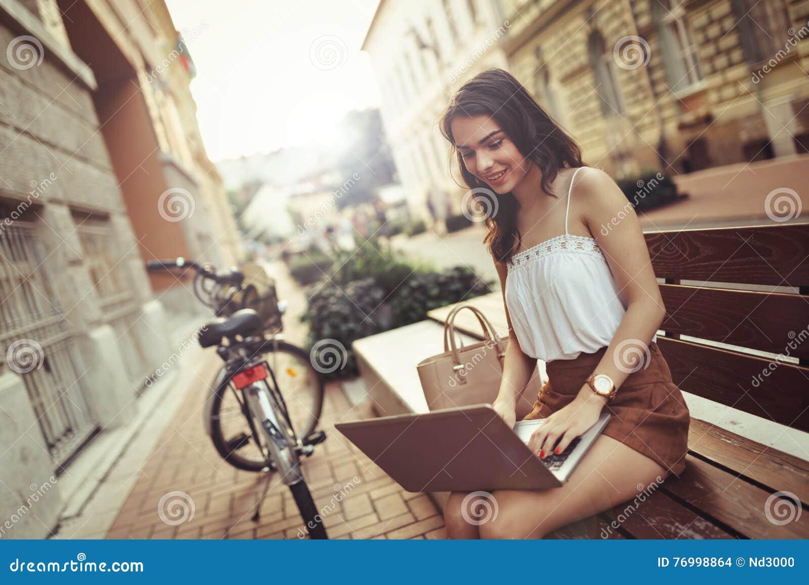 Beautiful woman using laptop outdoors