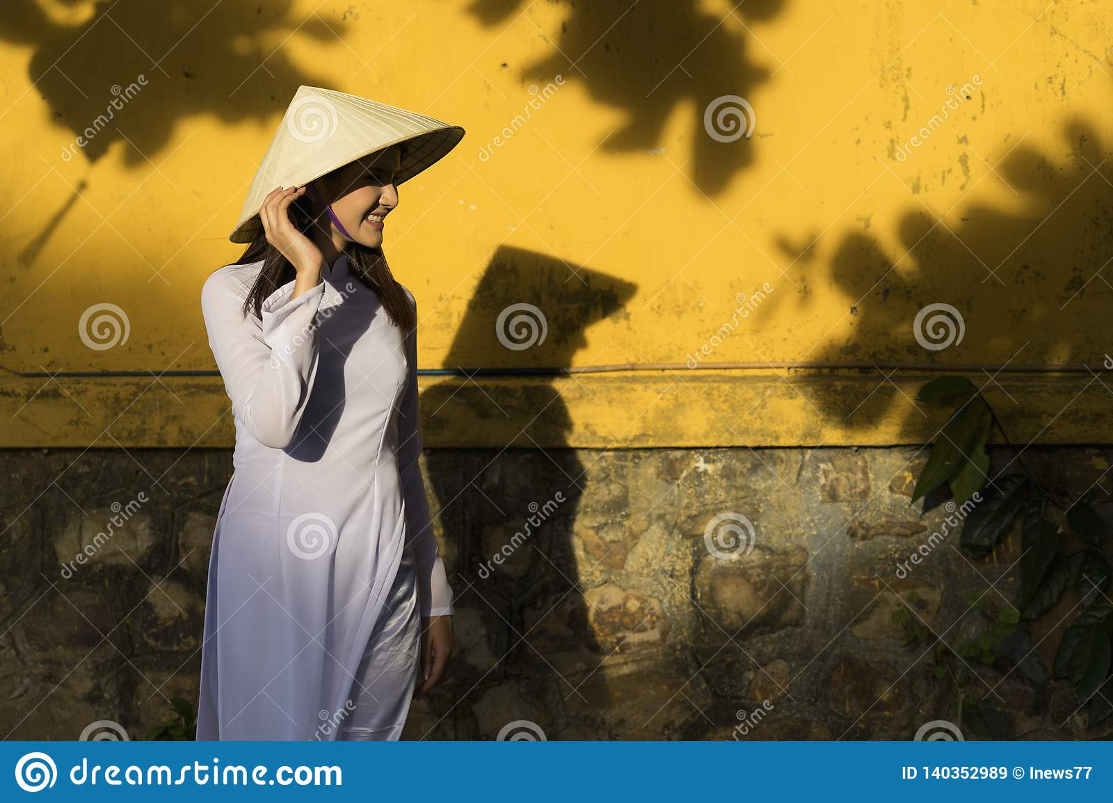 Beautiful woman with Vietnam culture traditional dress and holding hat, Ao dai is famous traditional costume, vintage style, Hoi