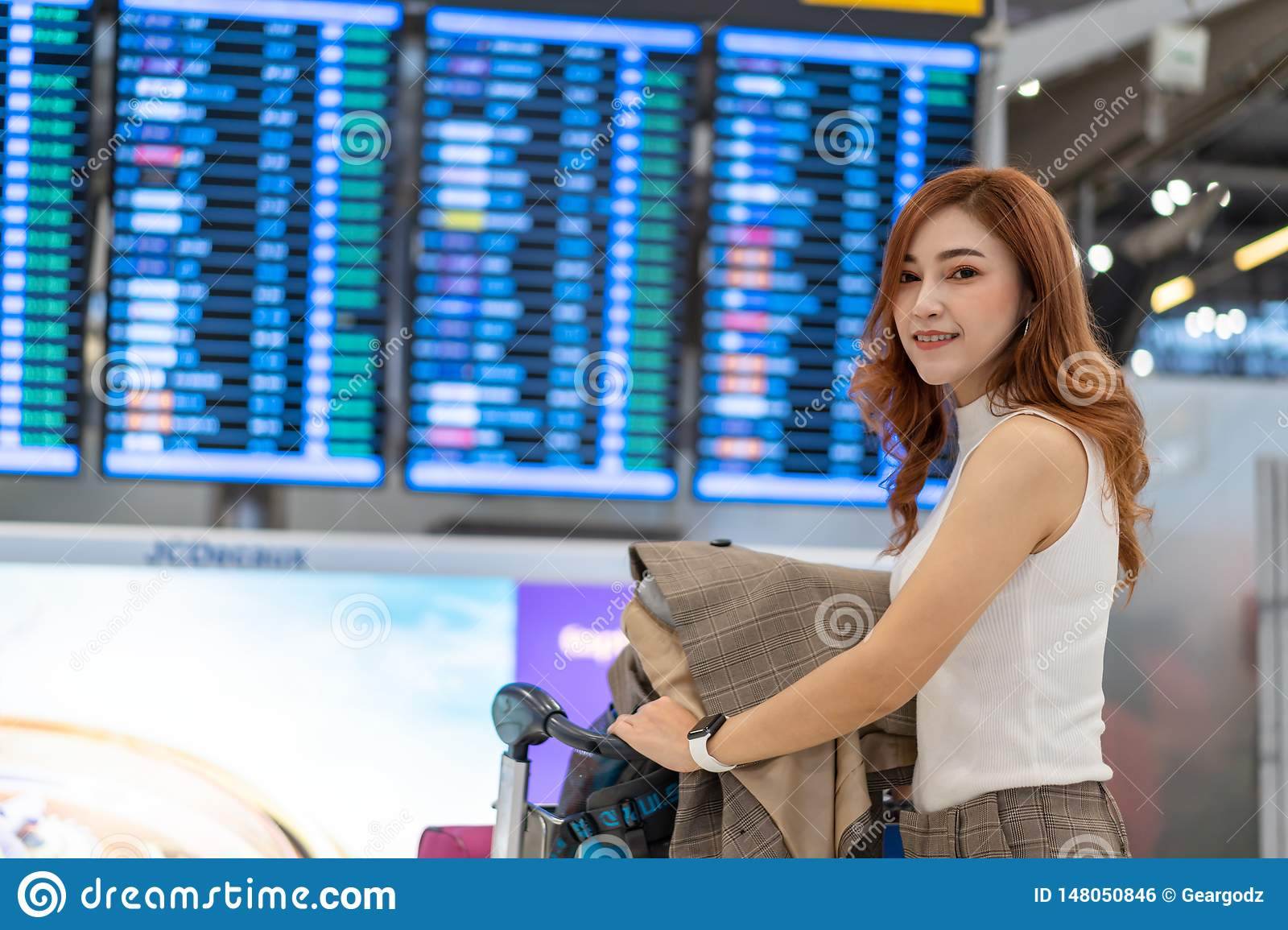 Woman waiting for flight with information board in airport