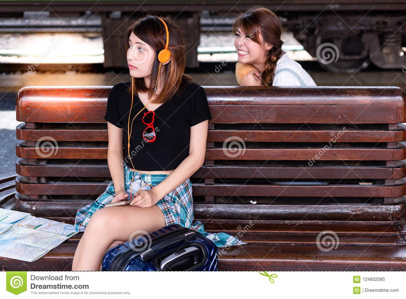 Beautiful woman is waiting her friend on wooden bench and listen