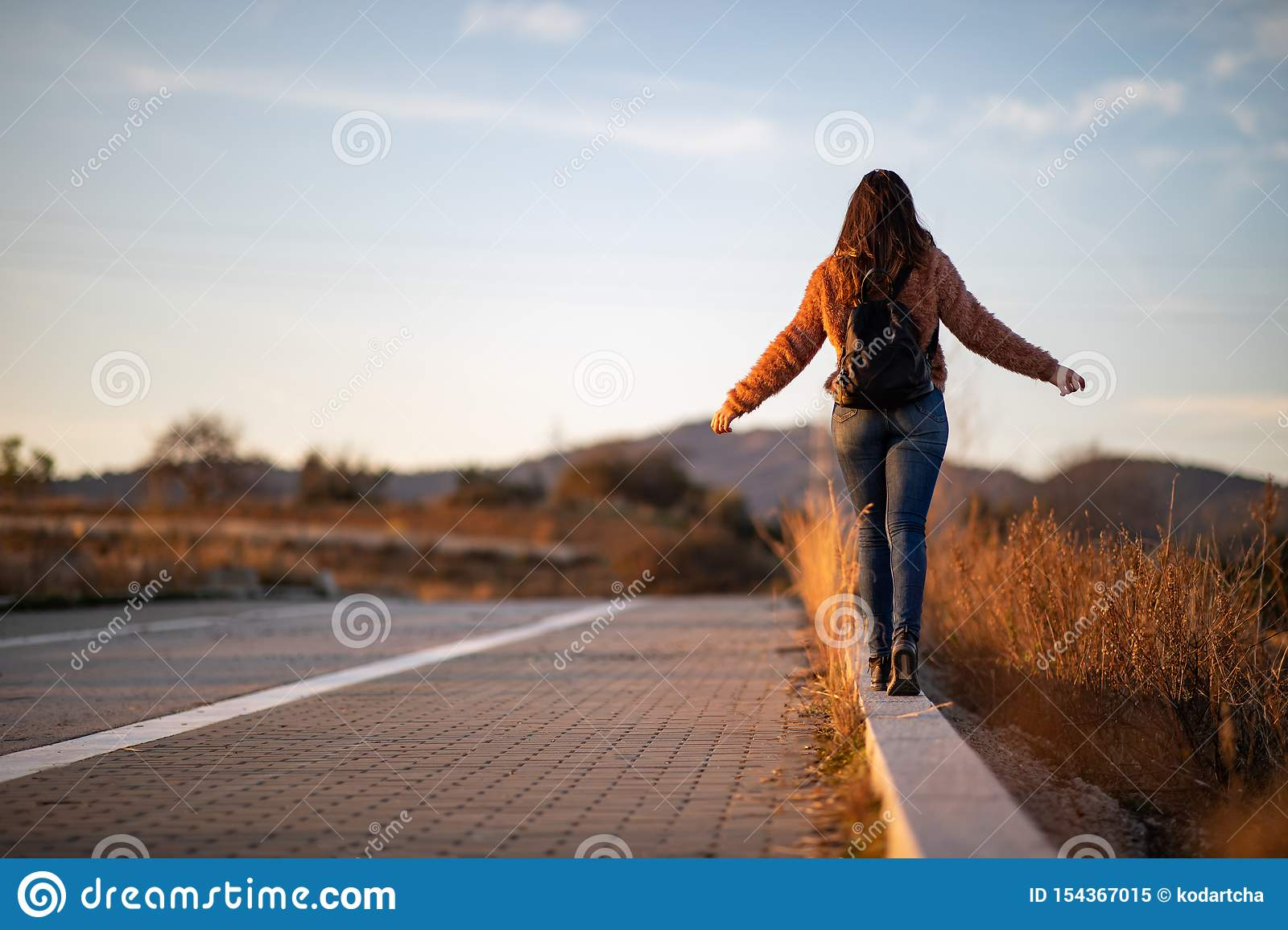 Beautiful woman walking and balancing on street curb or curbstone during sunset