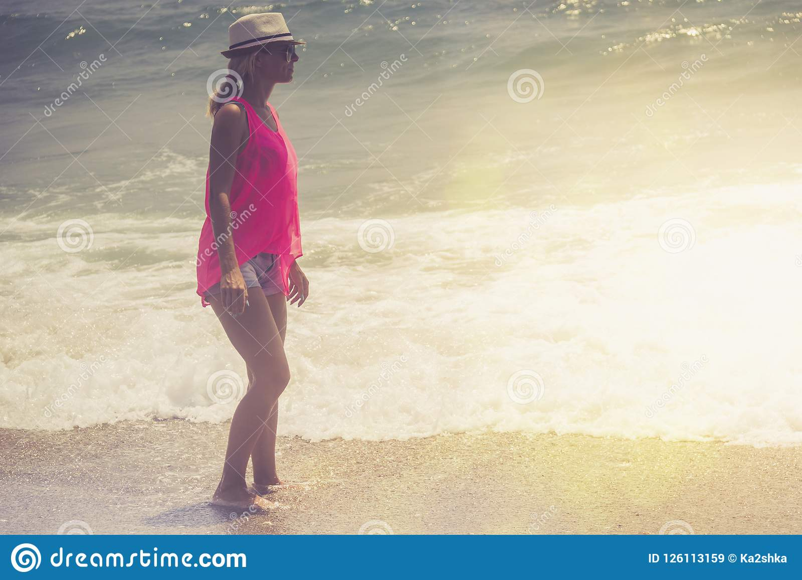 Beautiful woman walking on the beach.Relaxed woman breathing fresh air,emotional sensual woman near the sea, enjoying summer.Trave