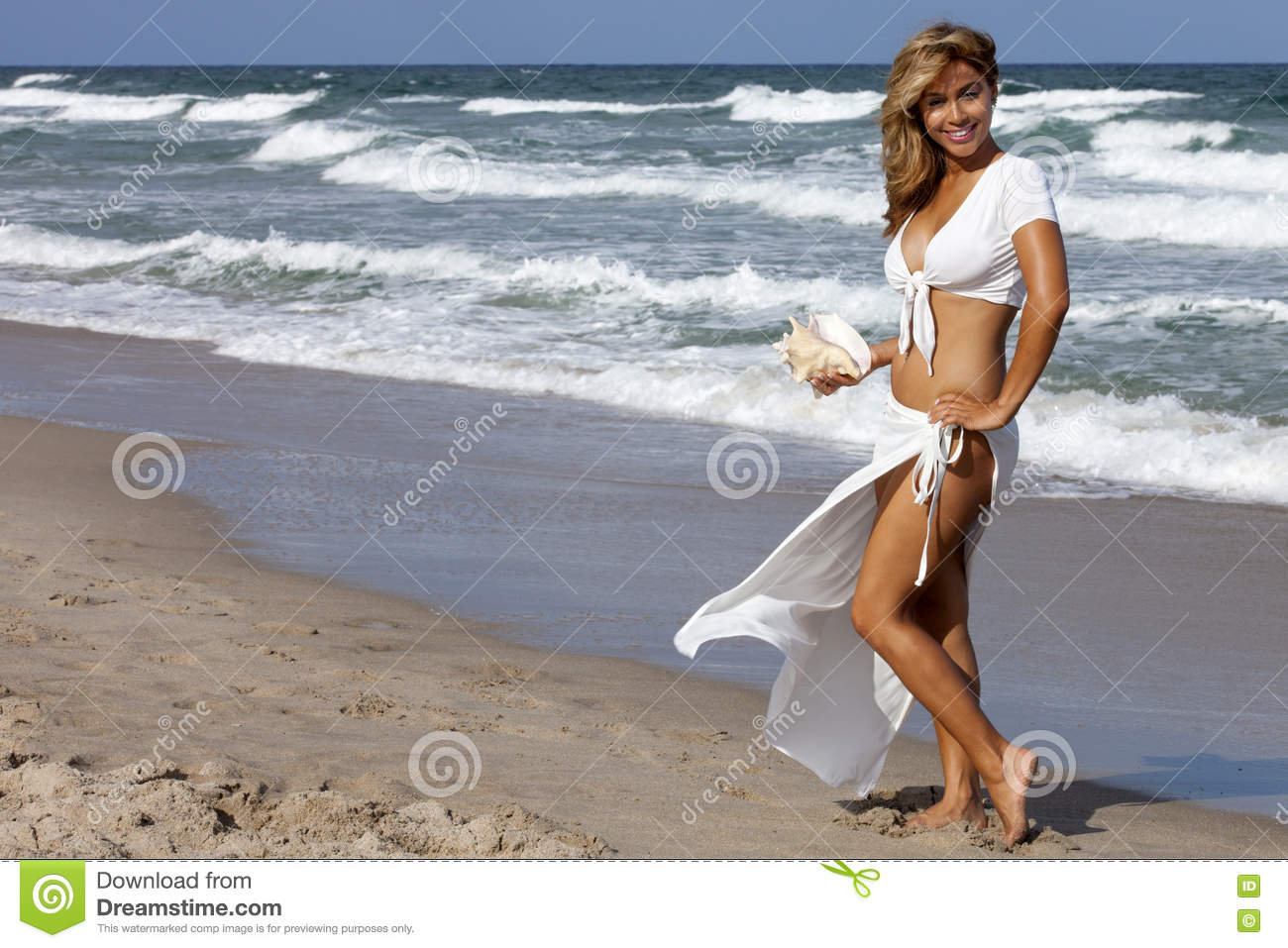 89f25d4b16 Beautiful woman walking on beach in a white outfit carrying a seashell