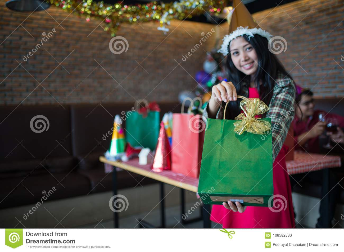Beautiful woman wear red dress and santa claus hat showing green gift bag on hand at restaurant, Christmas party