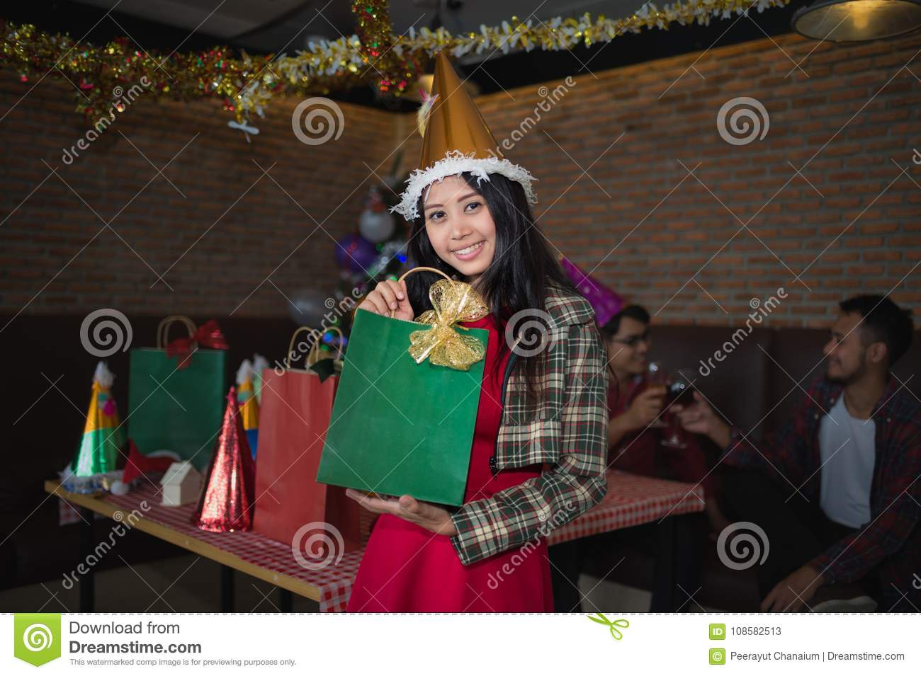 Beautiful woman wear santa claus hat showing green gift bag on hand in restaurant. concept of Christmas party and New year party.