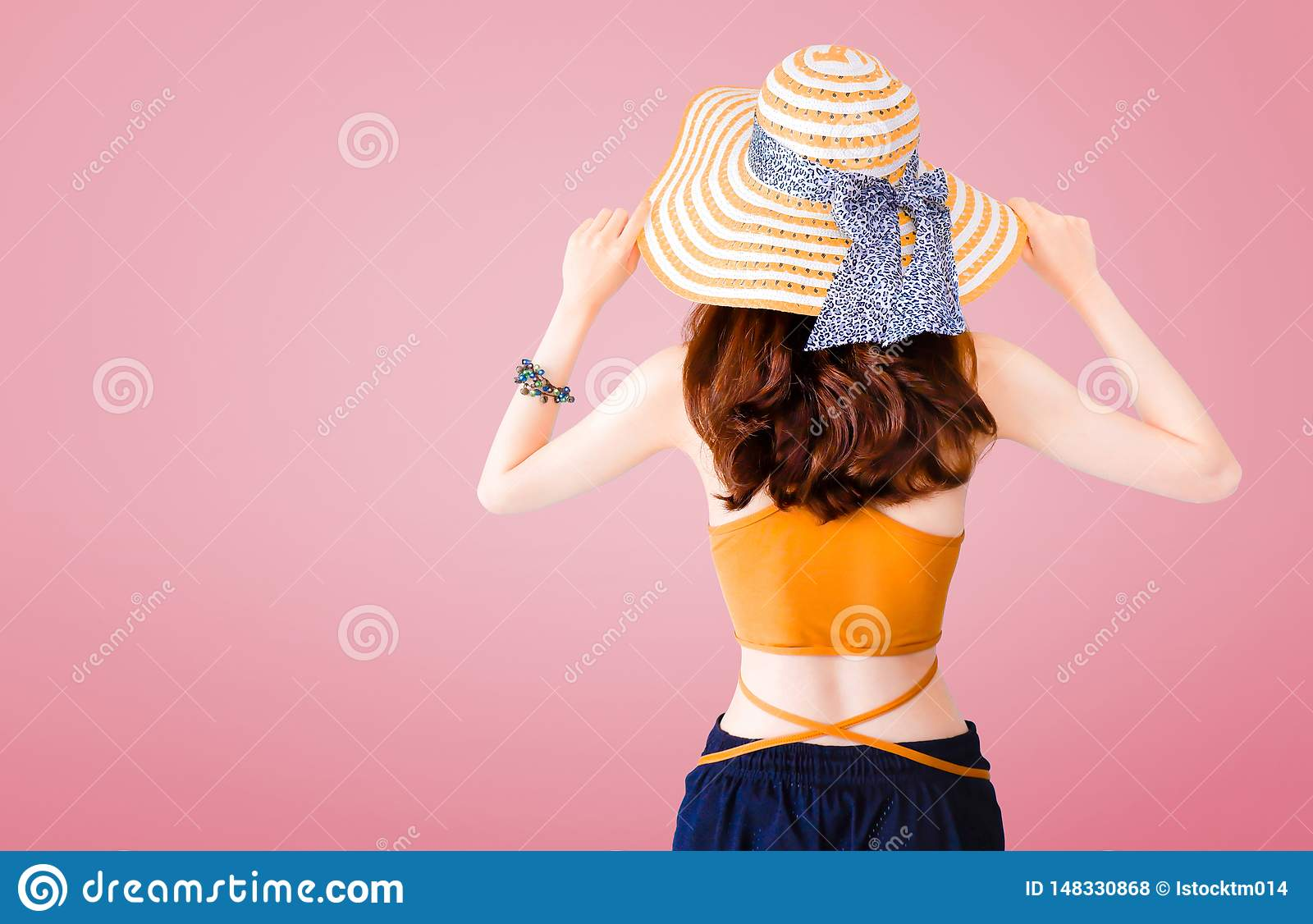 Beautiful woman wearing a straw hat and sexy suit on pink background with Summer concept