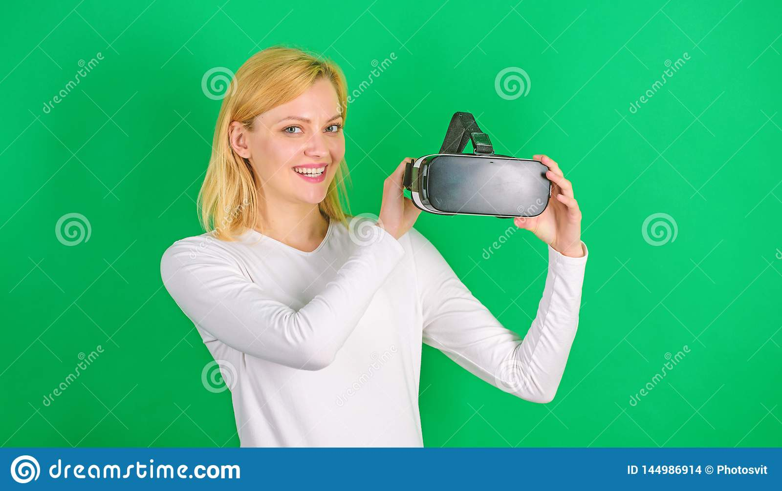 Beautiful woman wearing virtual reality goggles in studio. Person with virtual reality helmet  on green