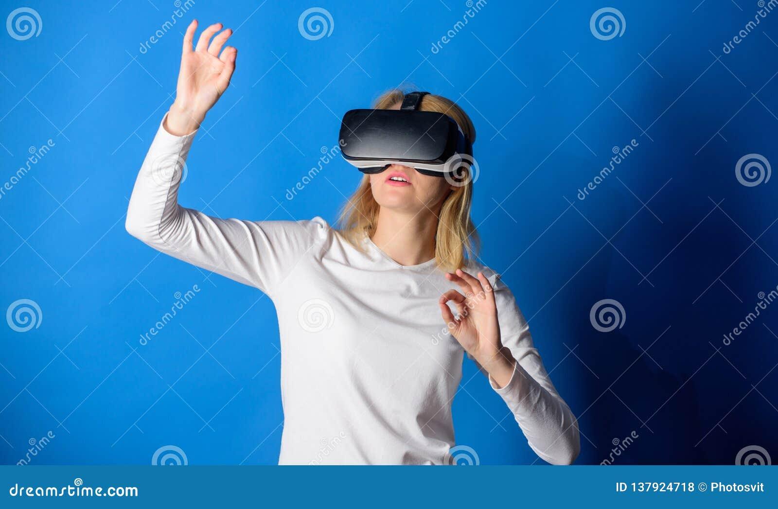 Beautiful woman wearing virtual reality goggles in studio. Woman using virtual reality headset. Happy woman exploring
