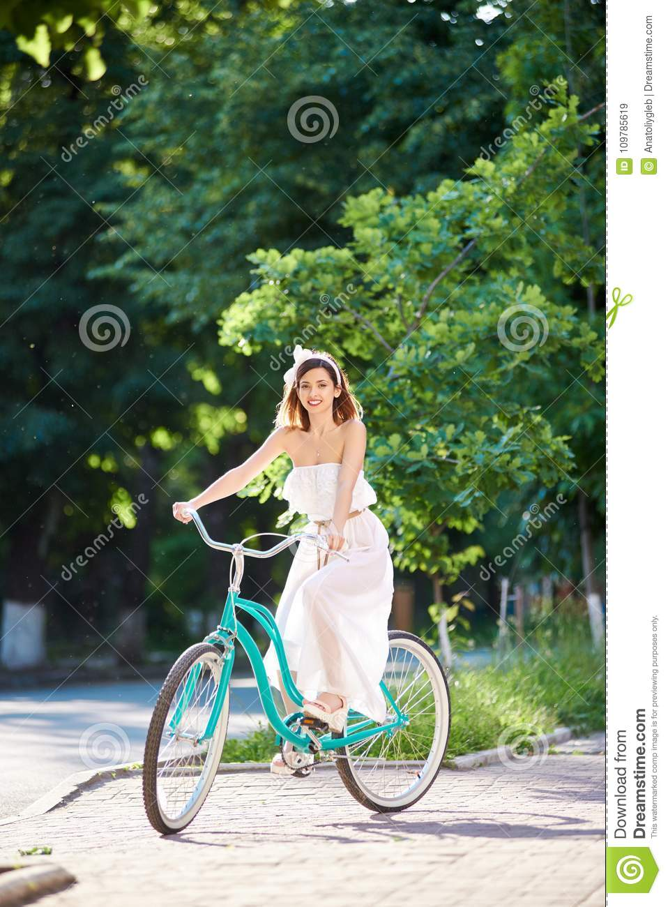 Beautiful woman in white dress riding vintage blue bike in a park.