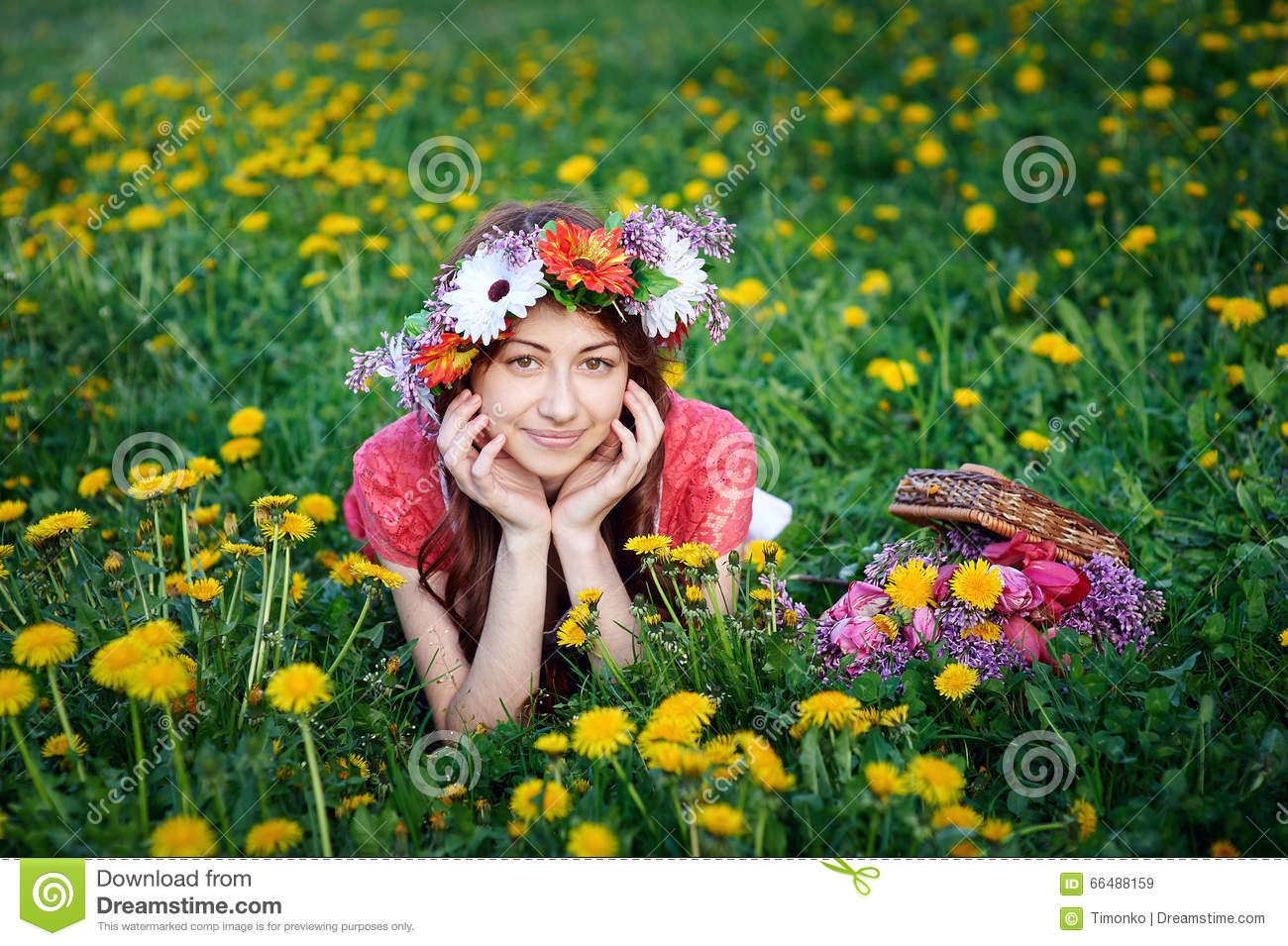 Beautiful woman in a wreath lying on the grass in a meadow