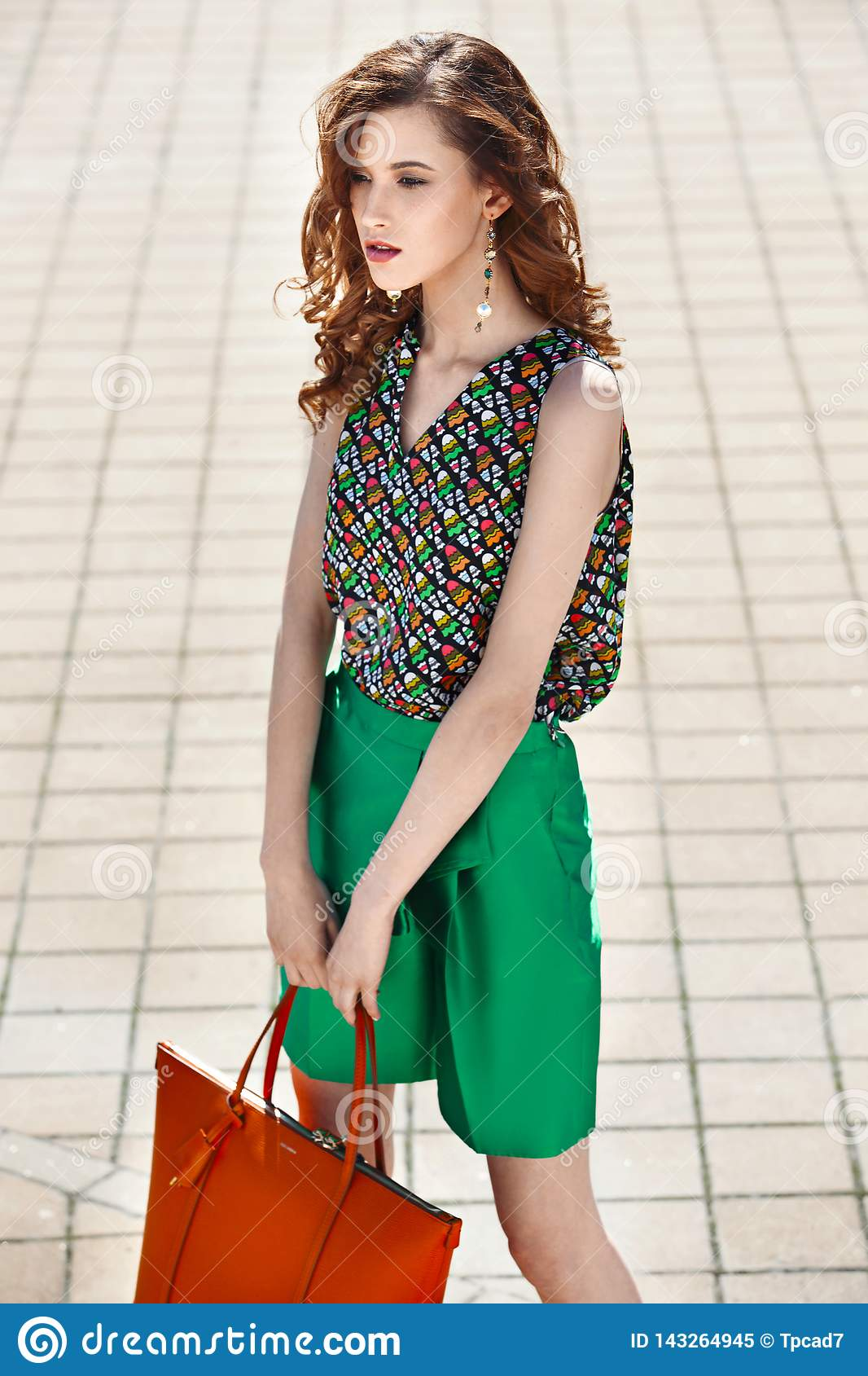 Beautiful women dressed in stylish green shorts and a bright top holding orange bag is walking in the city street on a