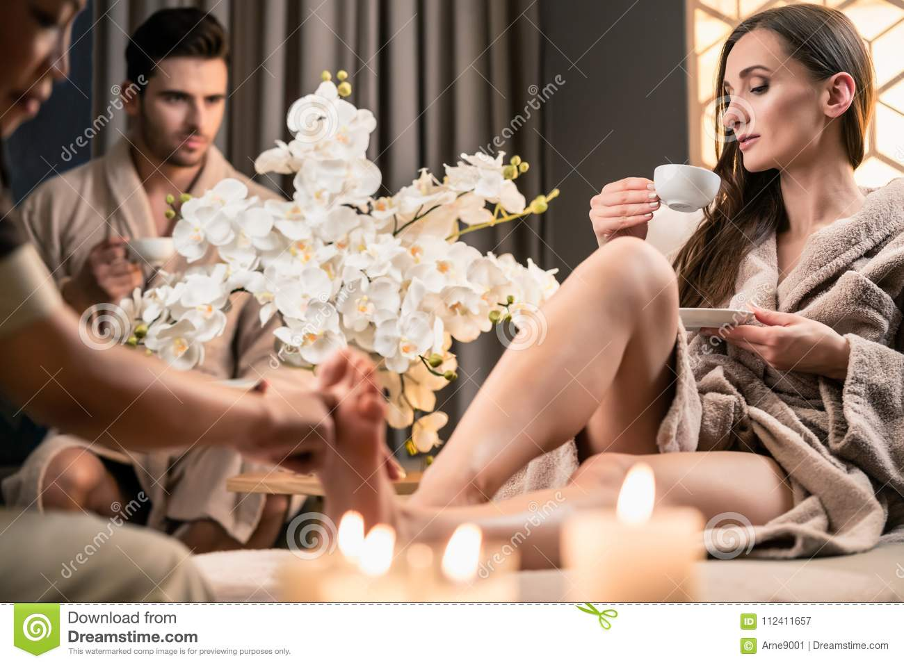 beautiful woman drinking tea during therapeutic foot massage stock