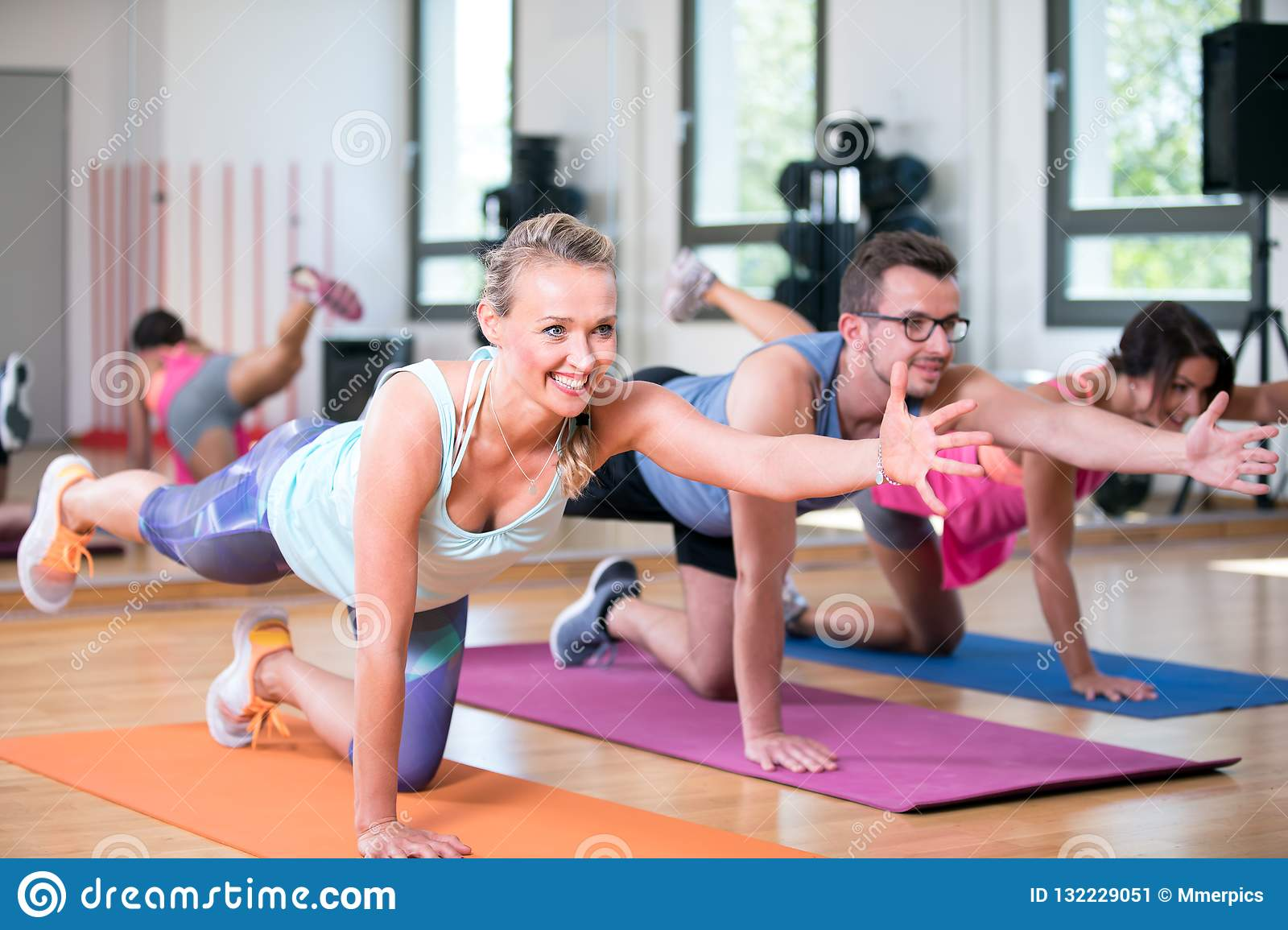 Beautiful women man group are doing sport fitness workout in a gym