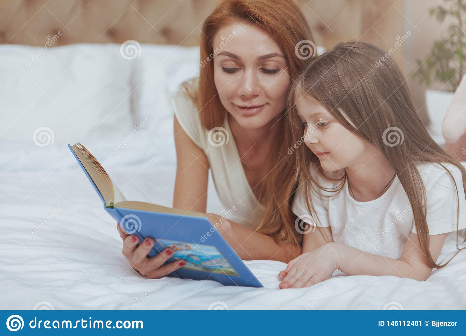 Charming woman reading a book to her little daughter
