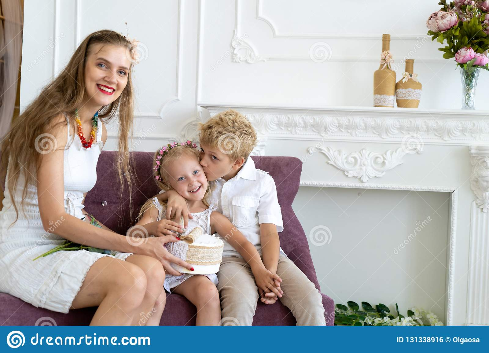Woman is sitting on the couch with her son and daughter