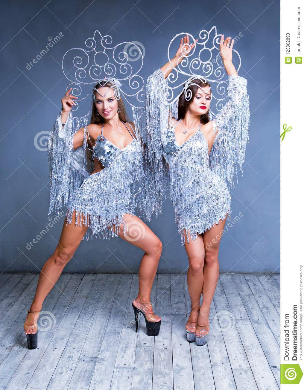 Beautiful women striptease dancers performing russian traditional folk  dance wearing sparkling silver costumes , isolated against white
