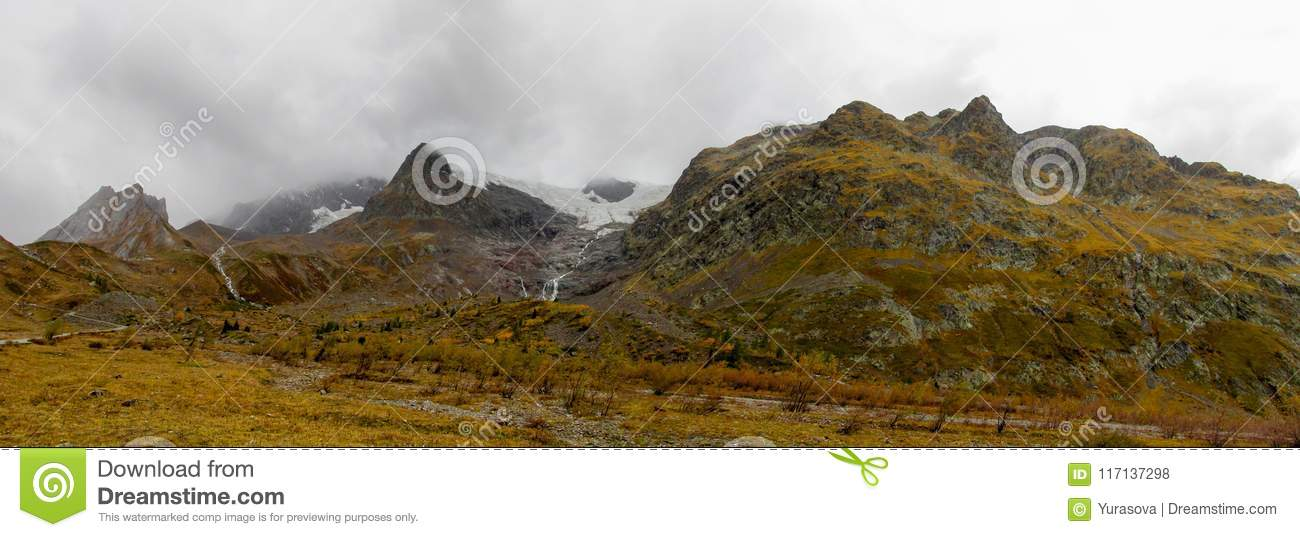 Beautiful yellow colors of autumn in the mountain valley long panorama