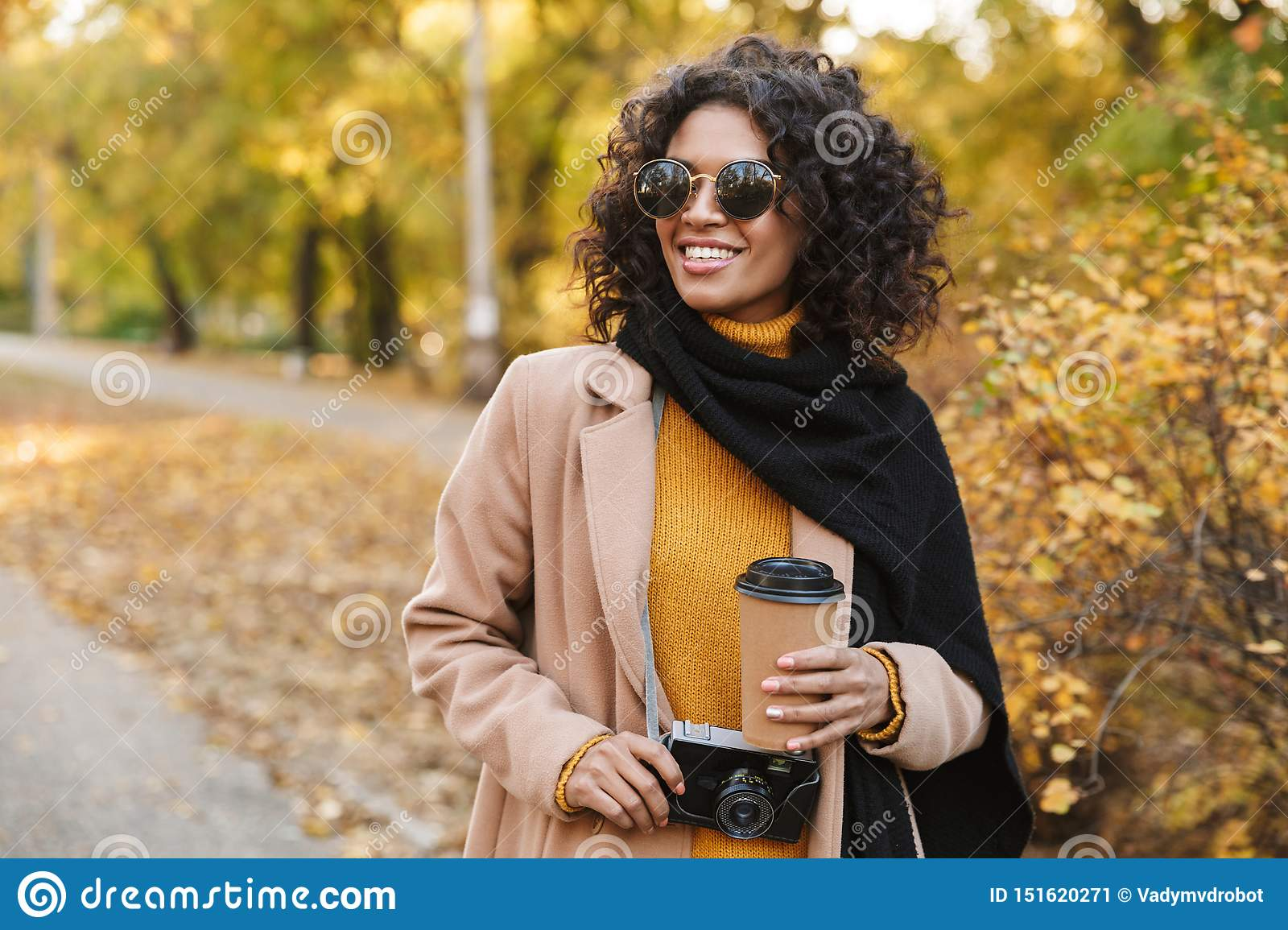 Beautiful young african woman walking outdoors in a spring park drinking coffee