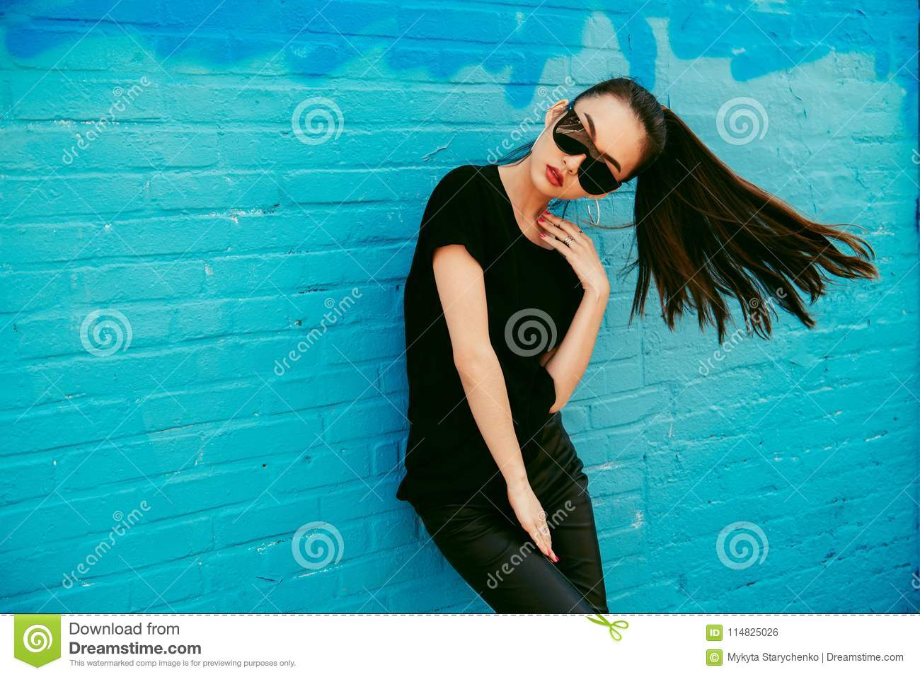 Beautiful young asian girl with long hair wearing sunglasses and black t-shirt posing in front of blue wall.