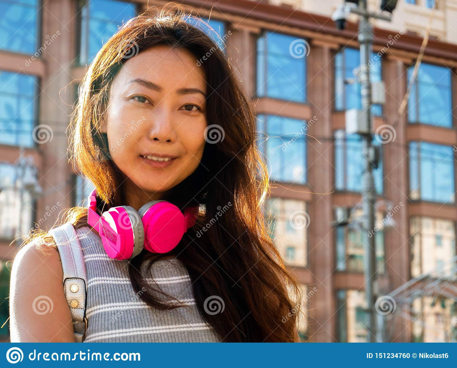 Beautiful young asian girl with tablet. Sunny summer day in the city standing with earphone.