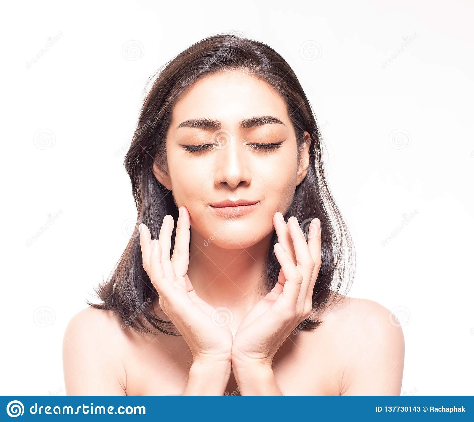 Beautiful young Asian woman with clear fresh skin touch her own face .  Facial treatment,