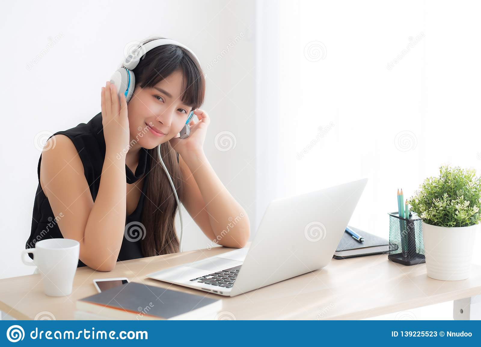 Beautiful young asian woman wear headphone smiling say hello using chat video call on laptop computer