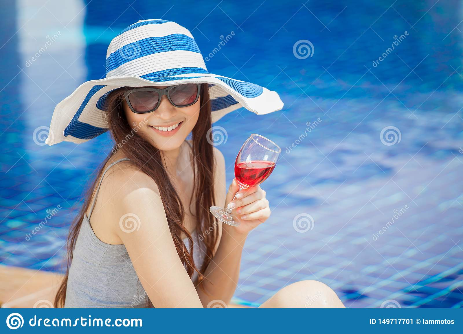 beautiful Young Asian women with beverages on summer party near the swimming pool .Happy girls in big hat and glasses relaxing