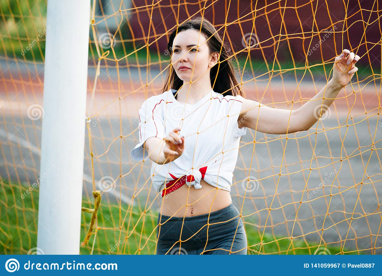 Beautiful young athletic woman in sportswear is training in stadium on background of a football goal. with football. she is happy