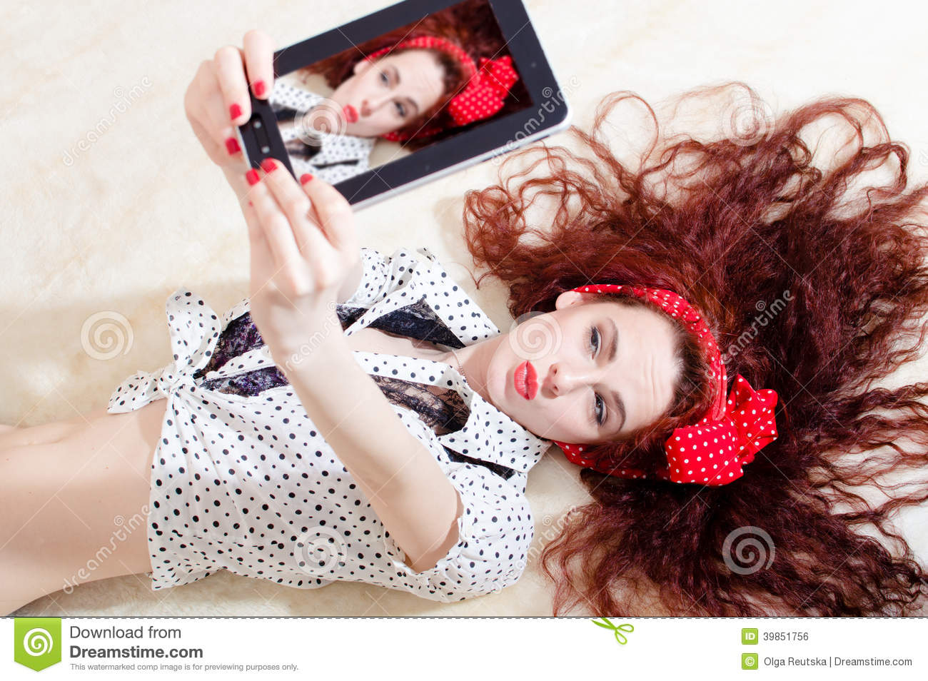 Beautiful young attractive woman pinup girl lying and taking selfy or selfie picture on digital tablet computer