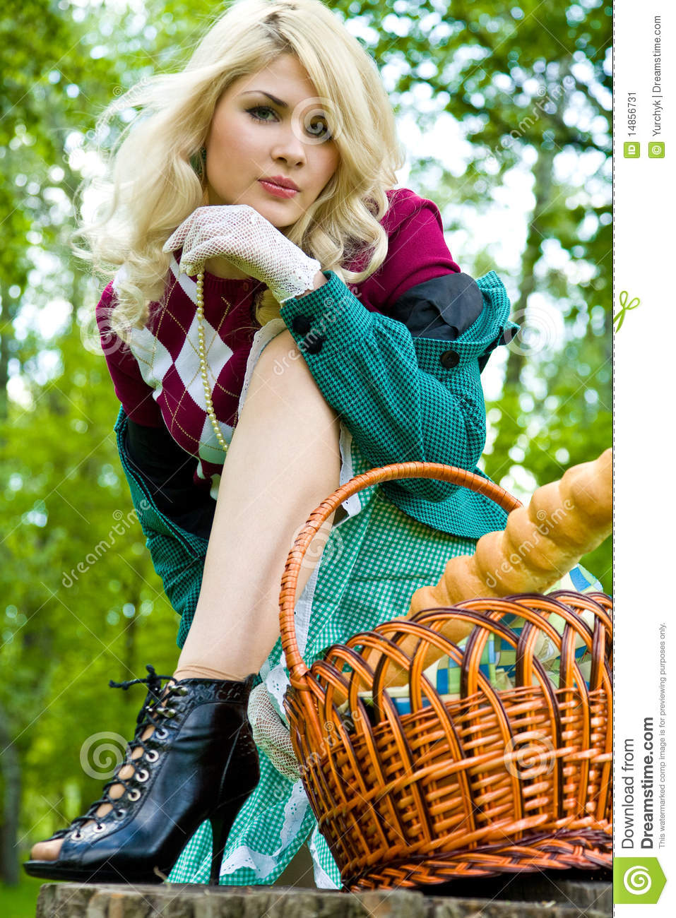 Beautiful young blond with basket in summer park