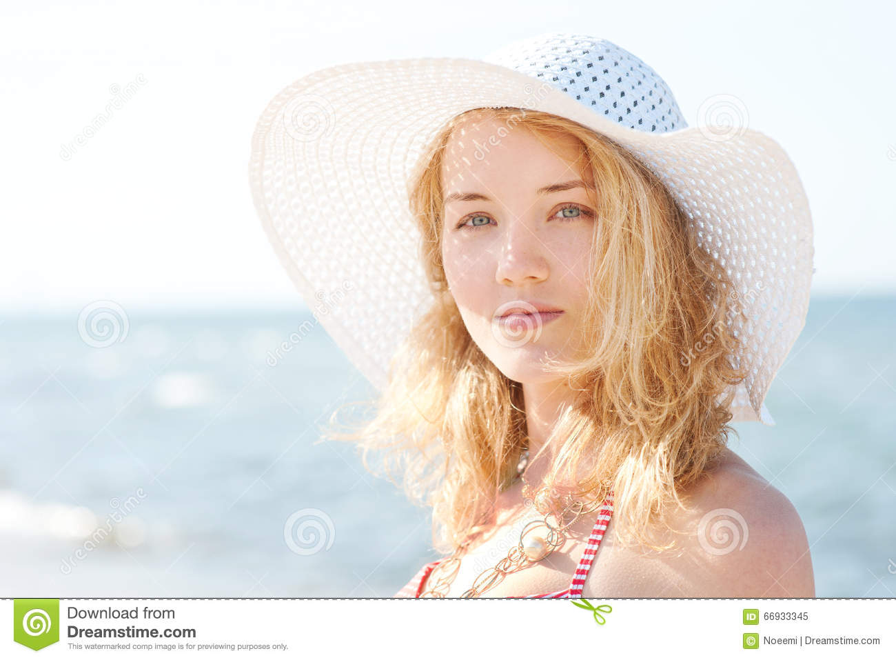 Beautiful young blond woman with beach hat