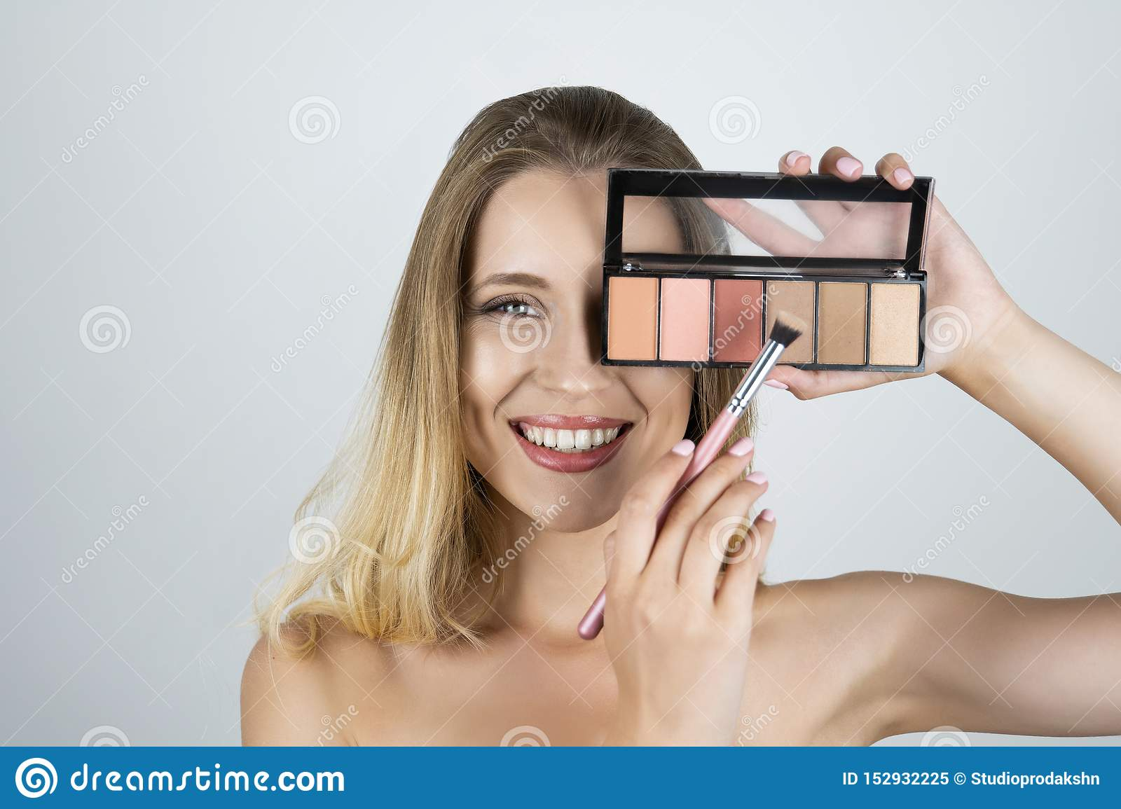 Beautiful young blond woman holding palette applying eyeshadow on the brush isolated white background