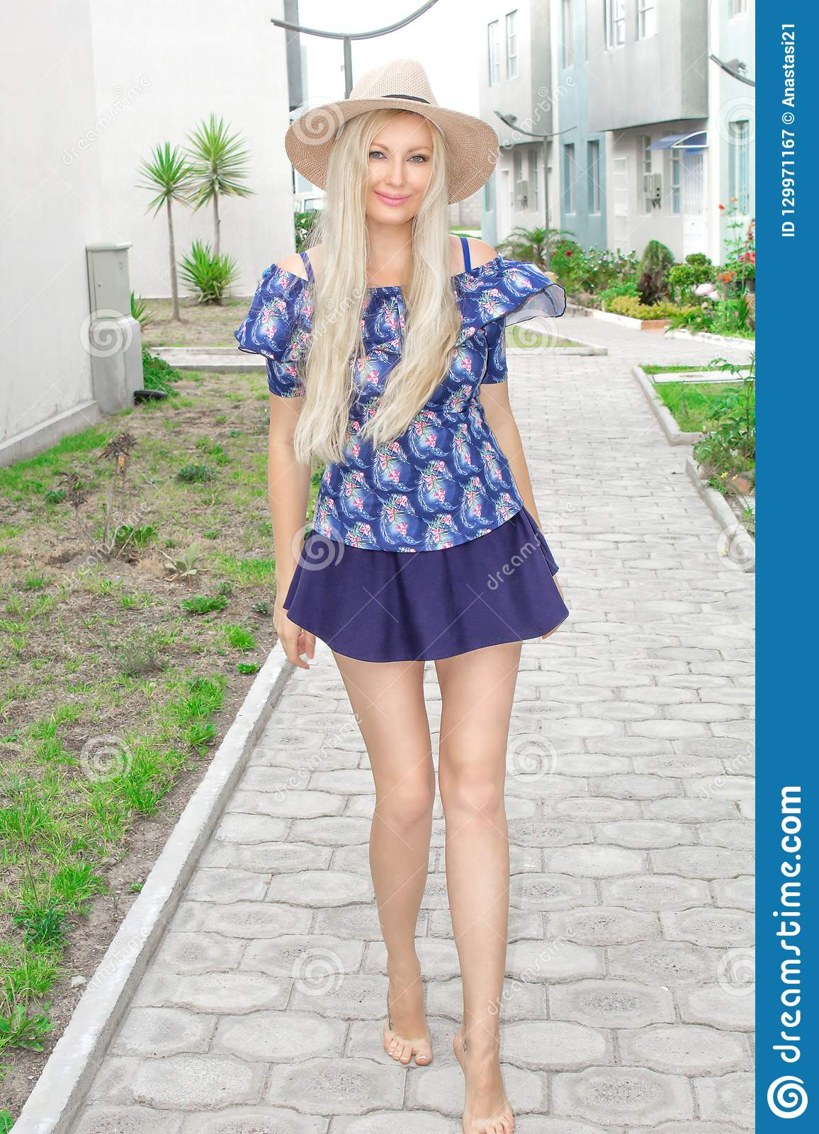 A beautiful young blond woman with long slim legs in a short skirt and hat is standing posing outdoors.