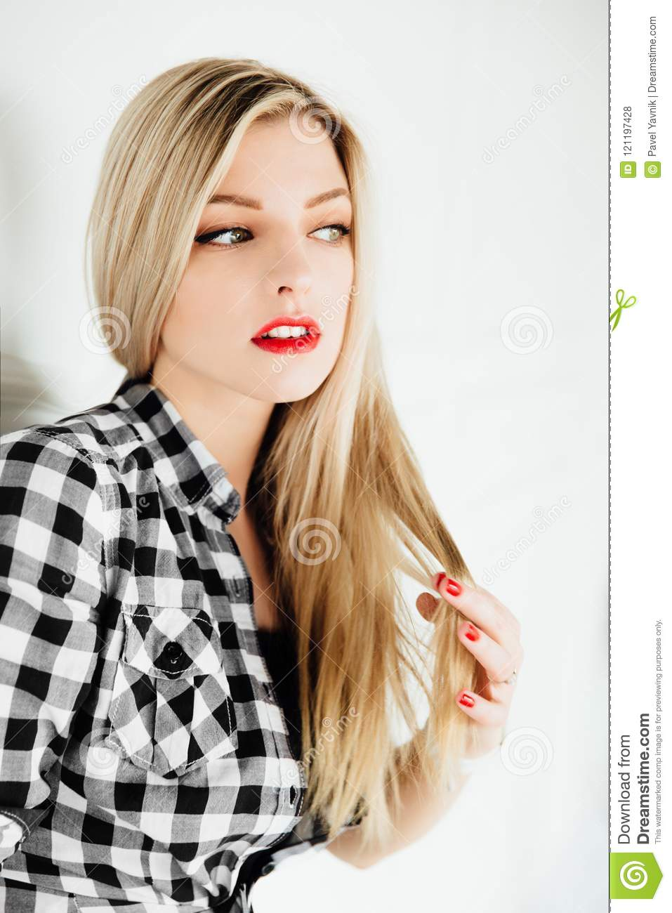 Beautiful young blond woman posing while leaning on interior studio wall.