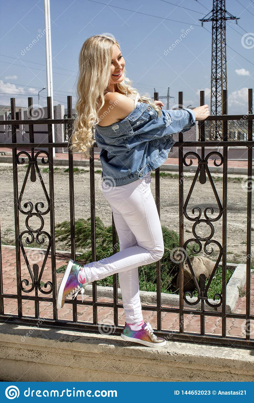 A beautiful young blond woman smiles, stands by the fence, and beautifully poses.