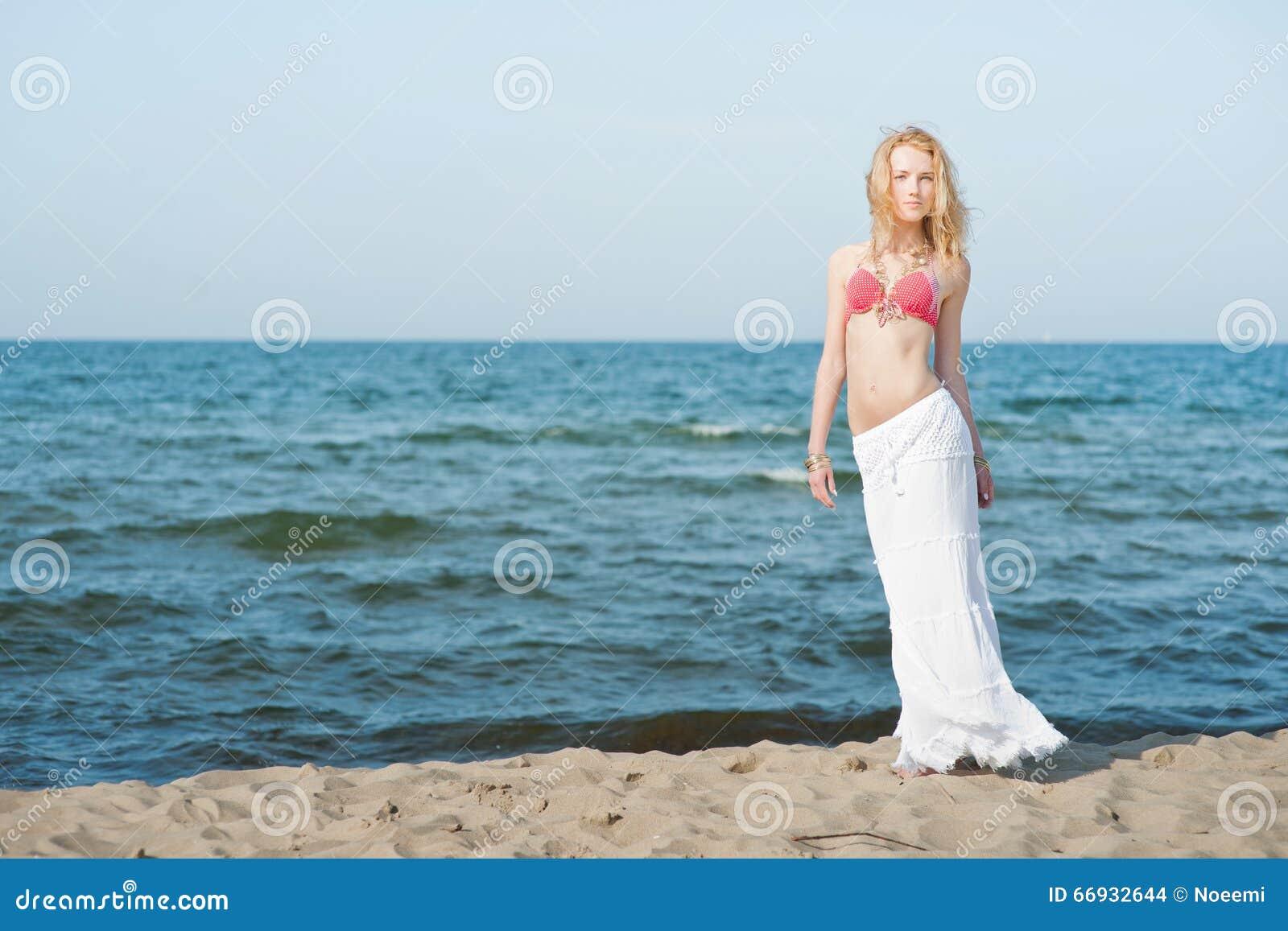 Beautiful young blond woman walking on a beach