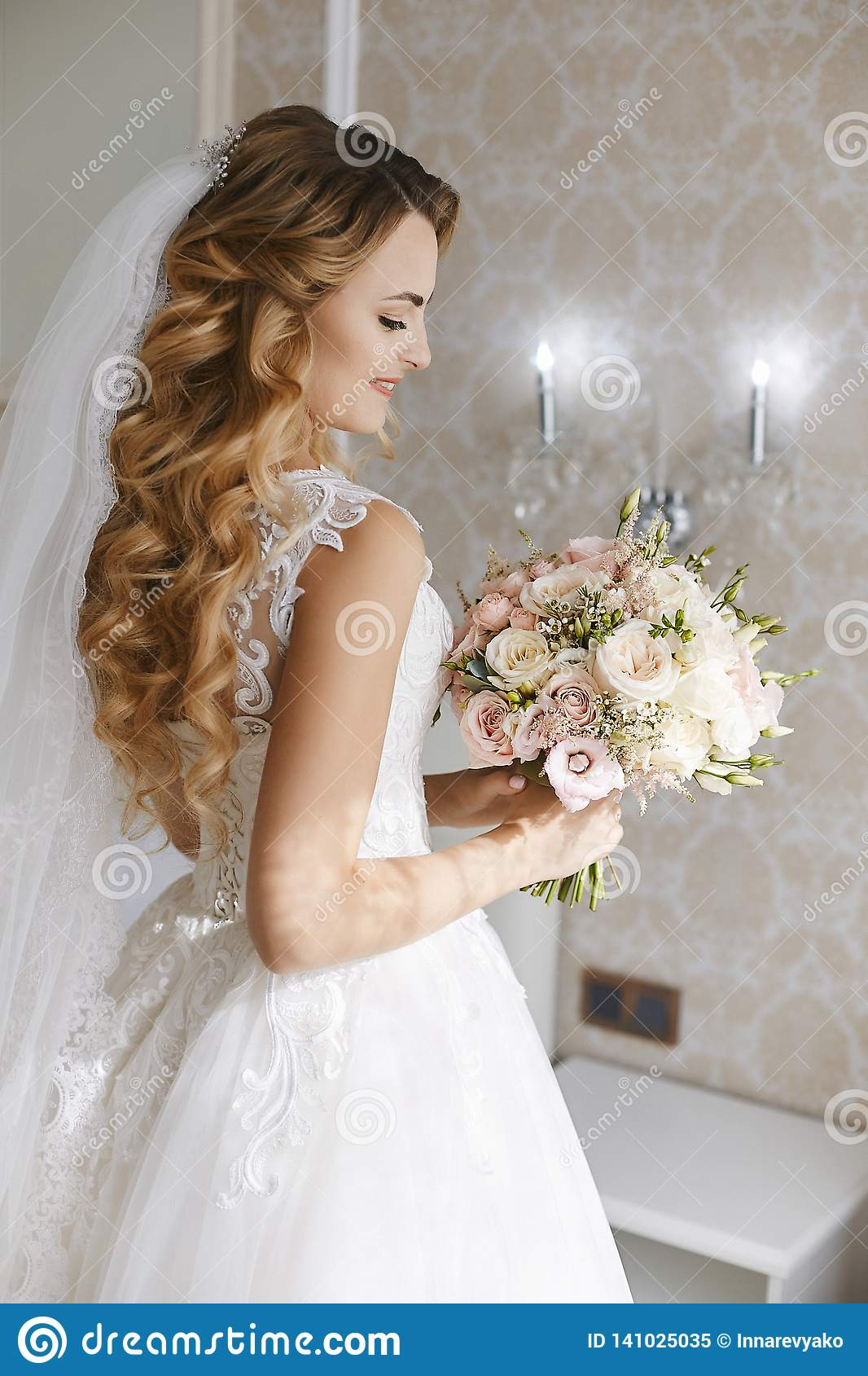 Beautiful young blonde bride with stylish wedding hairstyle in a white fashionable dress with a bouquet of flowers in