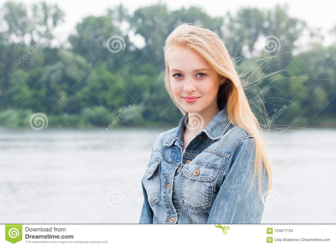 Beautiful young blonde woman in blue jeans with smile looking at camera on nature