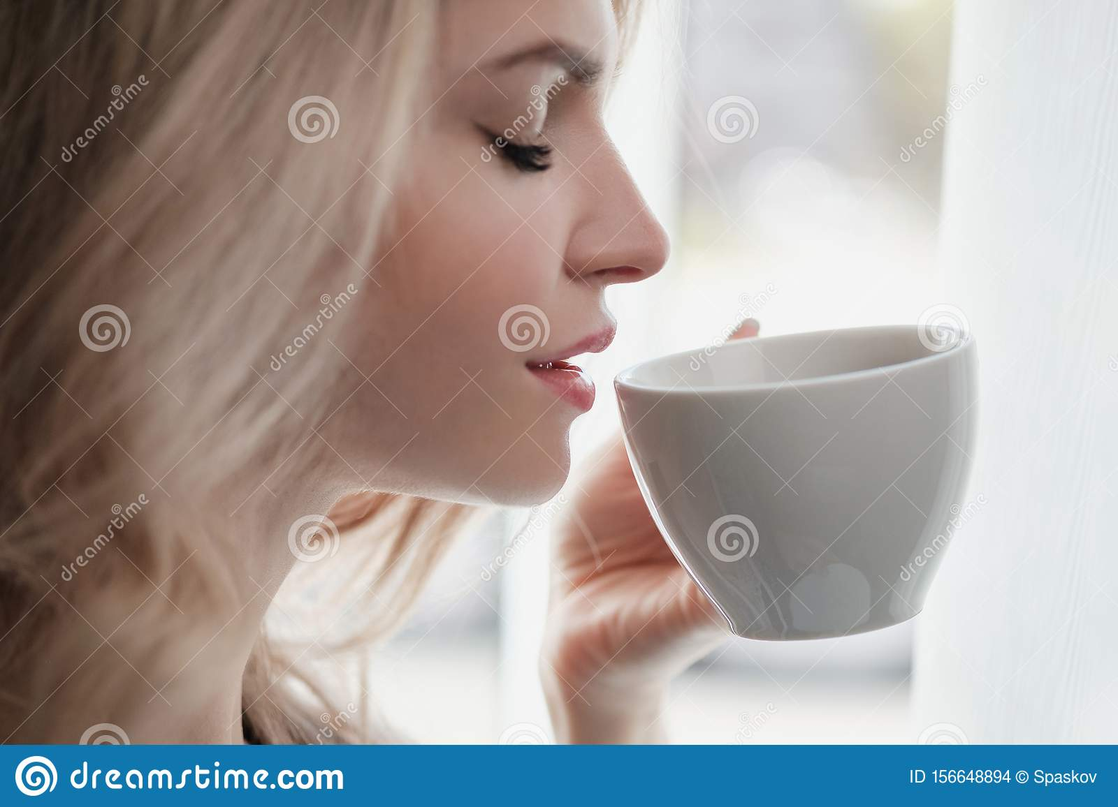 Beautiful young blonde woman in a blue robe by the window. Drinks coffee or tea from a white cup with a saucer. Morning