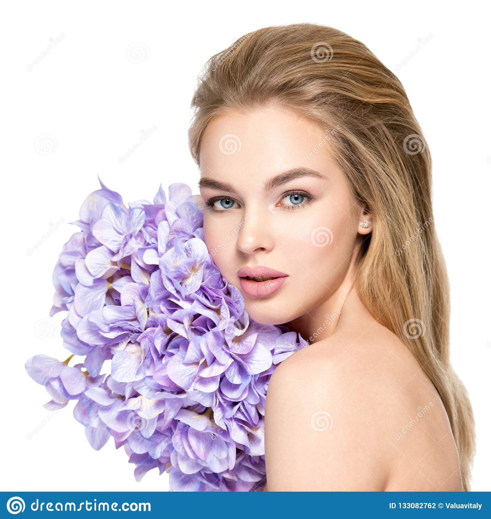 Beautiful young blonde woman with flowers near face