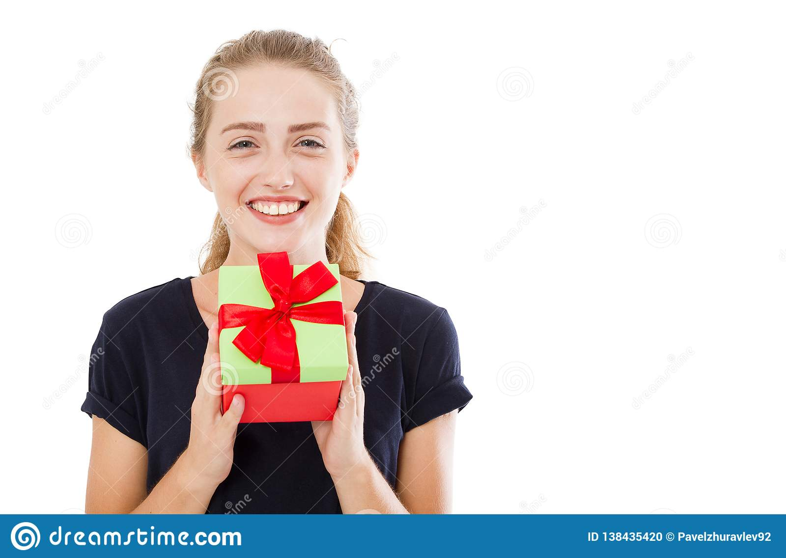 Beautiful young blonde woman holding gift over isolated background with surprise face pointing finger to himself,copy space
