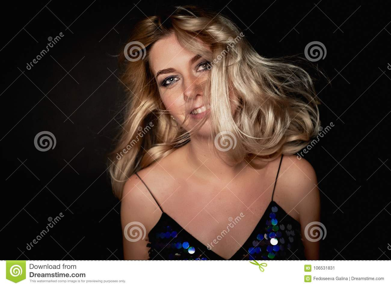 Beautiful young blonde woman with professional makeup Smokey eyes. Hair fluttering in dance
