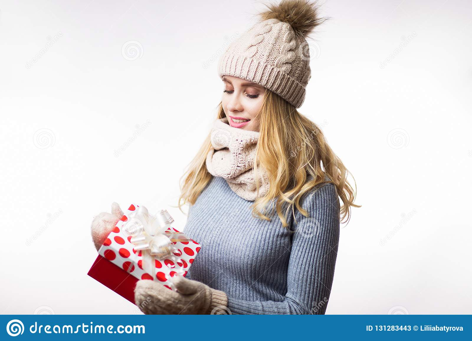 1c583533eab0 Beautiful young blonde woman in warm clothes with gift box on hand on white  background. Happy girl wearing beige knitted hat, scarf, mittens and grey  ...